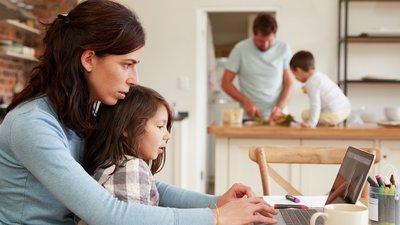 Nainen on tietokoneella lapsi sylissään