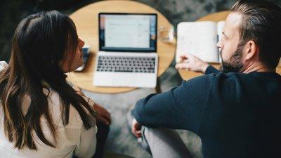 Nainen ja mies tutkivat tietoa tietokoneelta