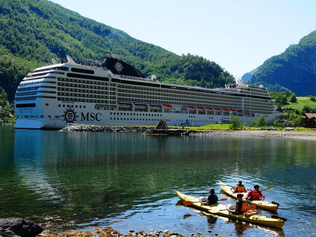 Foto av eit stort cruiseskip til kai i Flåm. I framkant av biletet ser vi to kajakkar som ligg nett utpå sjøen med to menneske i kvar.
