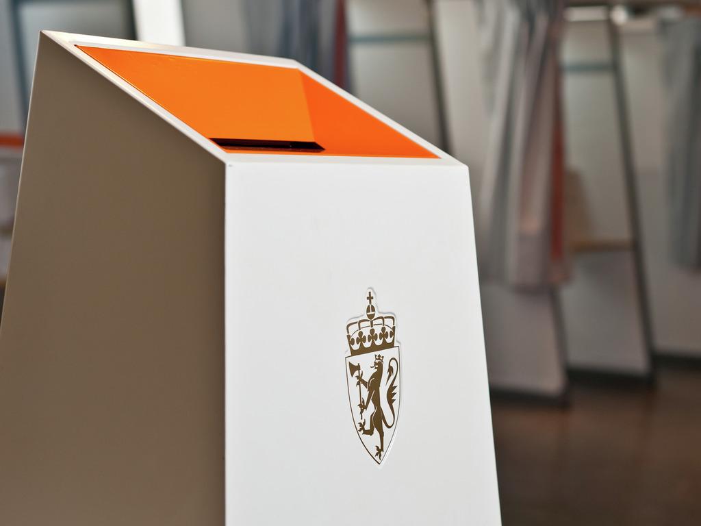 Foto av kvit og oransje valurne med riksvåpenet i gull på framsida. I bakgrunnen ser vi avlukke i eit stemmelokale.