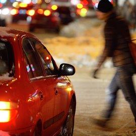 Jalankulkija kävelee auton edestä pimeällä ja talvisella kelillä