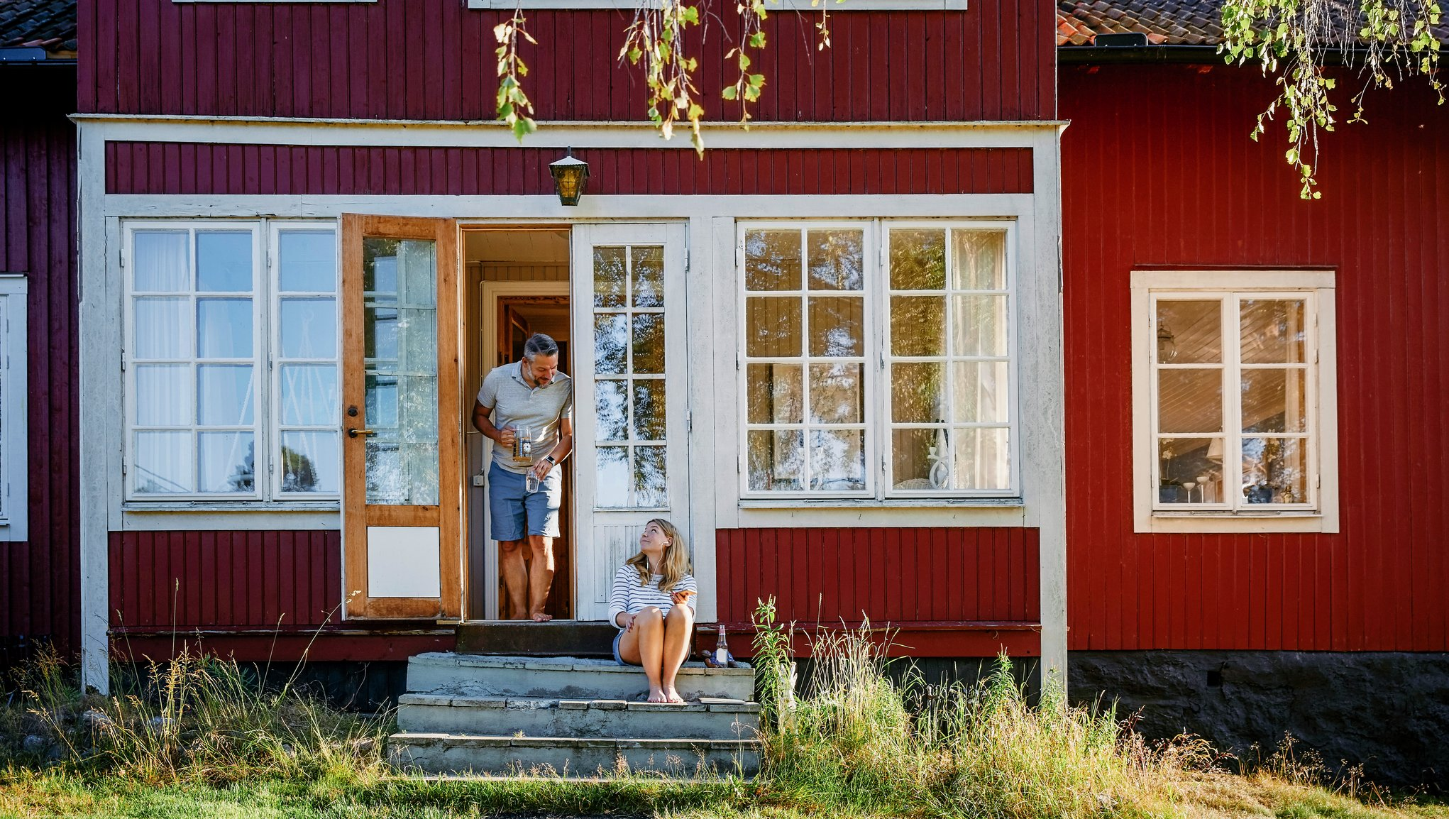 Et par utenfor et rødt hus