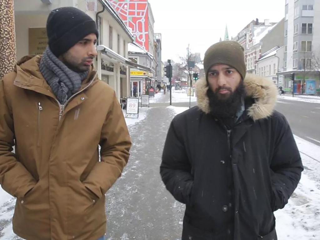 Foto frå filmen Den norske islamisten. Biletet syner regissør Adel Khan Farooq i samtale med Ubaydullah Hussain gatelangs i Oslo. Dei er kledde i tjukke jakkar og lurer, og det ligg litt snø på fortauet.