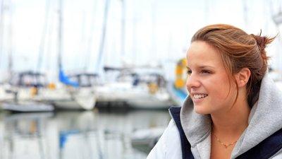 Nainen satamassa, purjeveneitä taustalla
