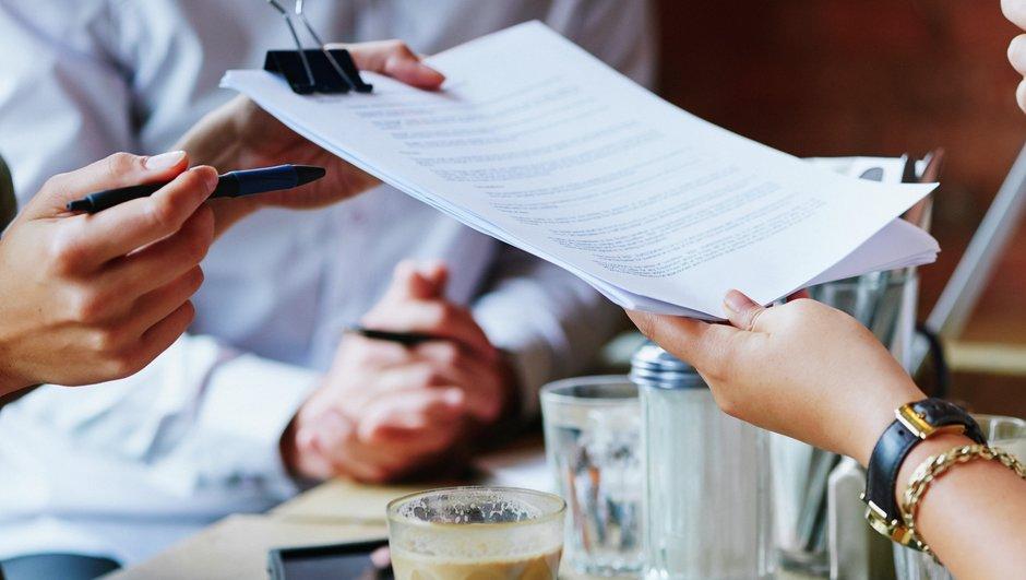 Mennesker rækker dokumenter til hinanden.