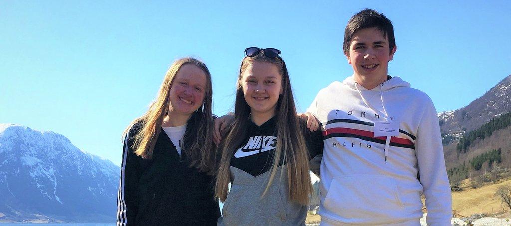 Foto av dei tre ungdomane, Lisa Horpen, Marthe Teigen Refsnes, Leander Sunde, framfor Jølstravatnet på Skei.