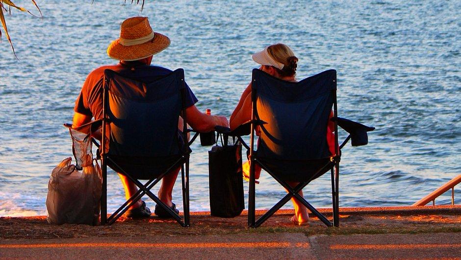 Lomaileva pariskunta meren äärellä