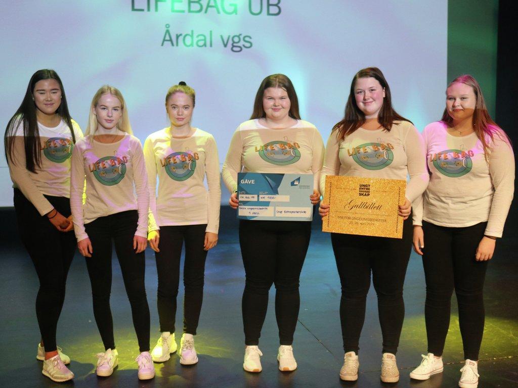 Foto av ungdomsbedrifta Lifebag UB frå Årdal vidaregåande skule. Det er seks jenter med svarte bukser og kvite t-skjorter med teksten Lifebag. Ei av dei held ein sjekk på 1000 kroner og ei held ein plakat der det står Gullbillett til NM for ungdomsbedrifter.