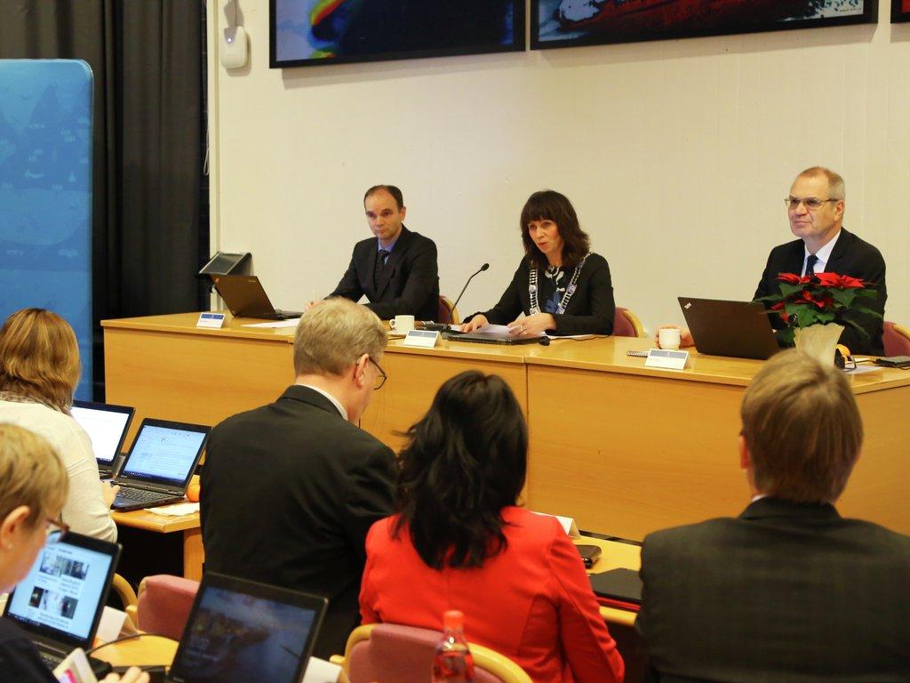 Jenny Følling, Tore Eriksen og Svein Hågård sit ved møteleiarbordet under opninga av fylkestinget i Firdasalen på Fylkeshuset i Leikanger. Politikarar sit i salen ved mot møteleiarbordet.