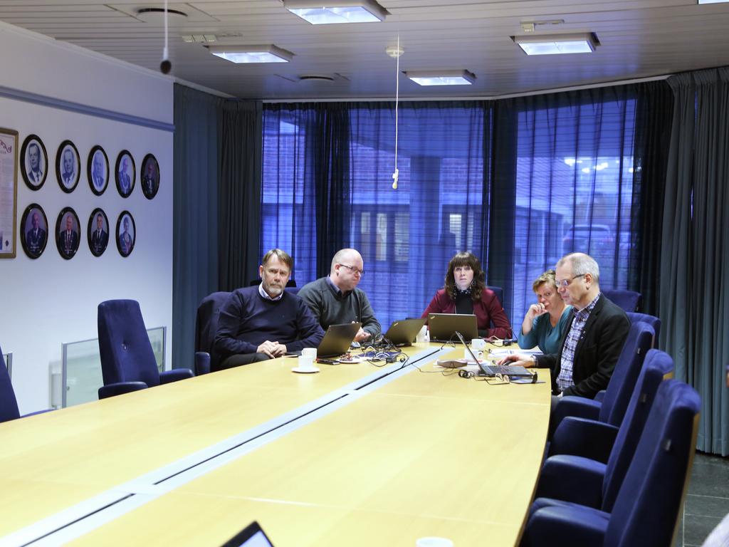 Politikarar og fylkesråmannen sit ved eit møtebord, alle med pc`ar.