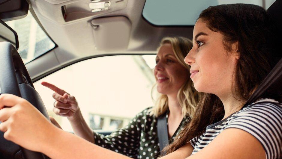 Vanhempi nainen neuvoo nuorempaa naista pienessä autossa