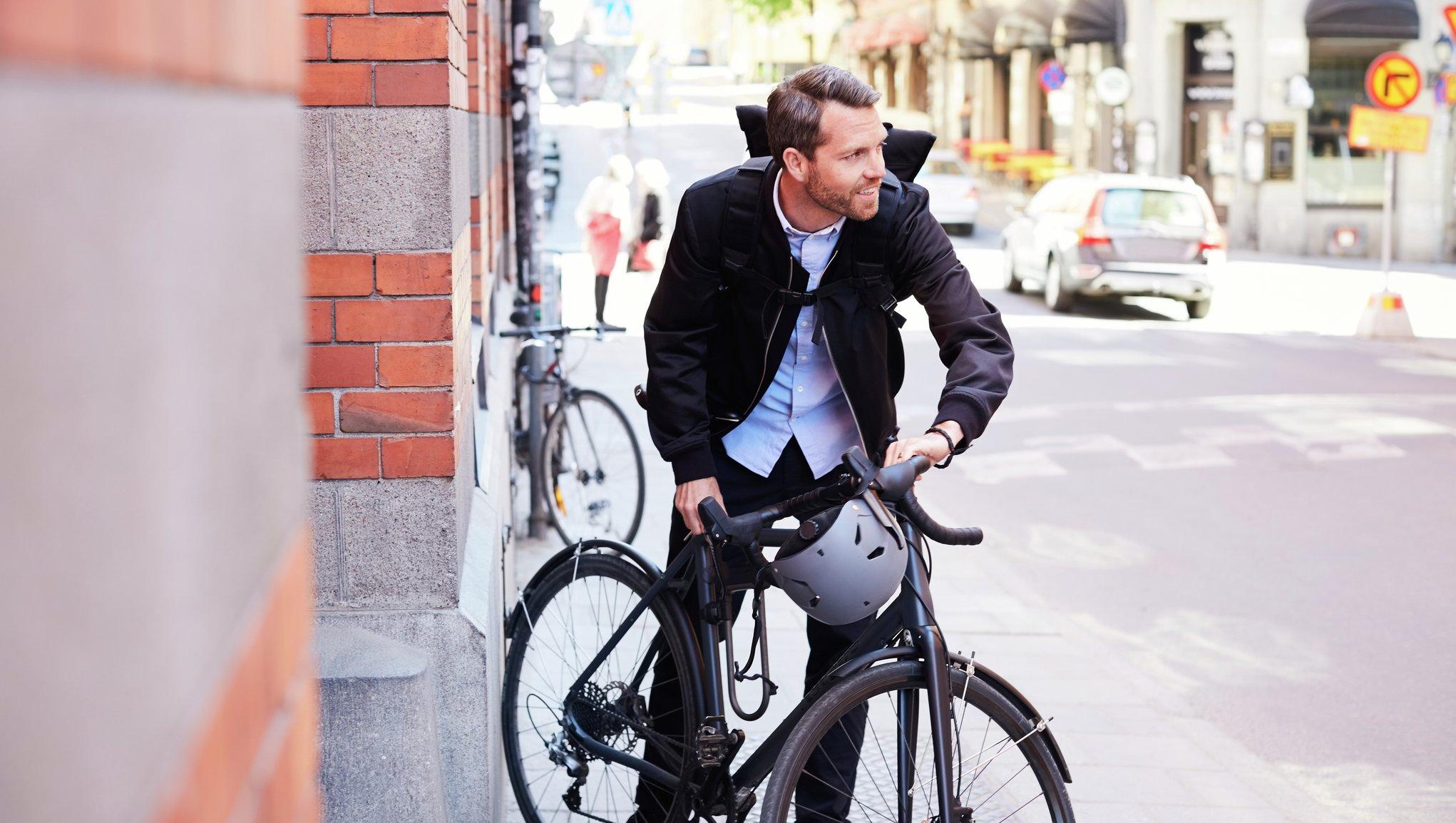 Mies on lähdössä polkupyörän kanssa liikkeelle kadulla