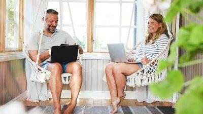 Mies ja nainen istuvat terassilla läppärit sylissään