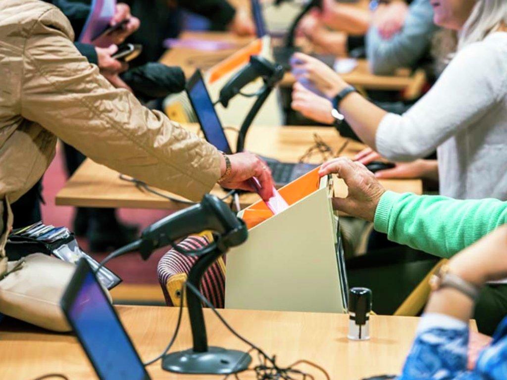 Foto frå eit vallokale, der nokon puttar ein stemmeseddel i valurna.