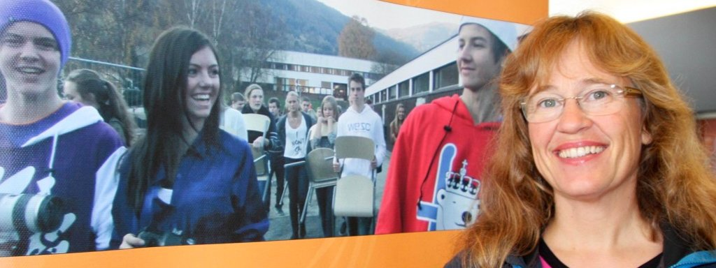Portrett av elev- og lærlingombodet i Sogn og Fjordane, Venke Nordeide. Ho står framfor ein plakat med tittelen hennar og bilete av skuleungdomar.