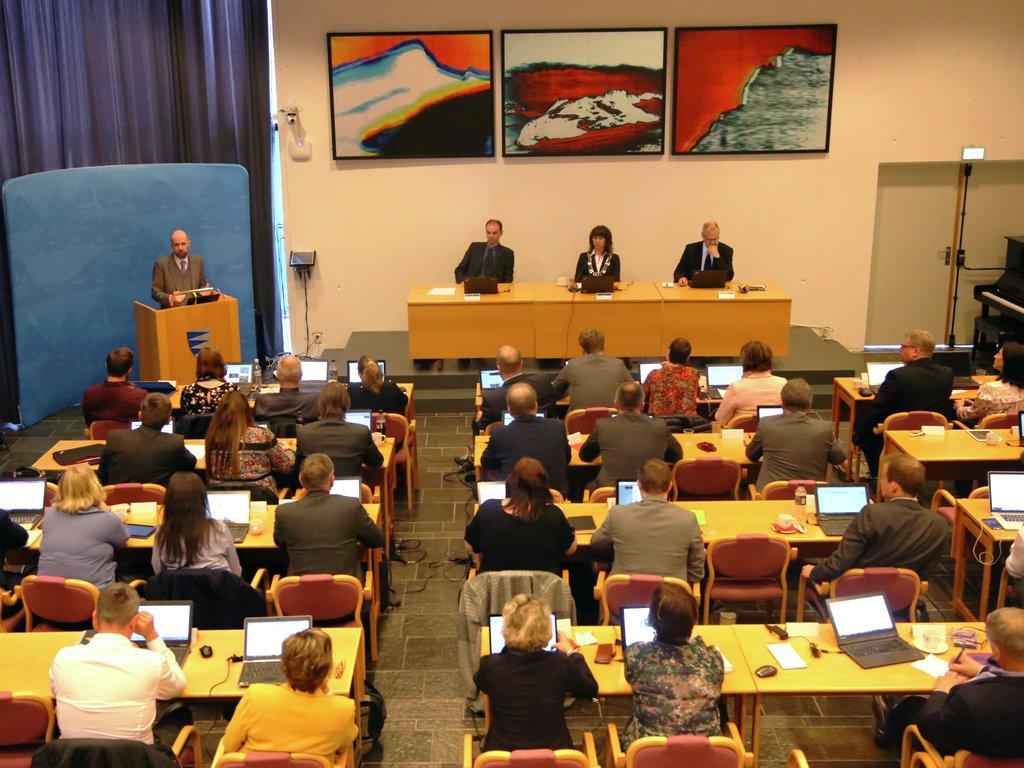 Bilete frå møte i fylkestinget. Mange politikarar i salen, ein på talarstolen. Fylkesordførar og fylkesrådmann sit fremst.