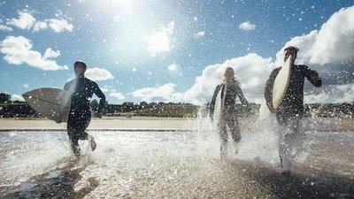 Surffaajia juoksee rantaveteen