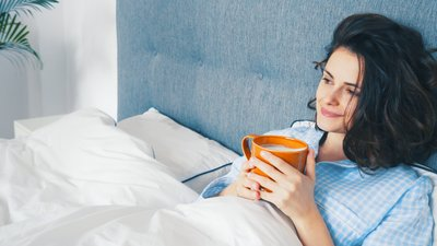 Nainen makaa sängyssä pidellen teekuppia