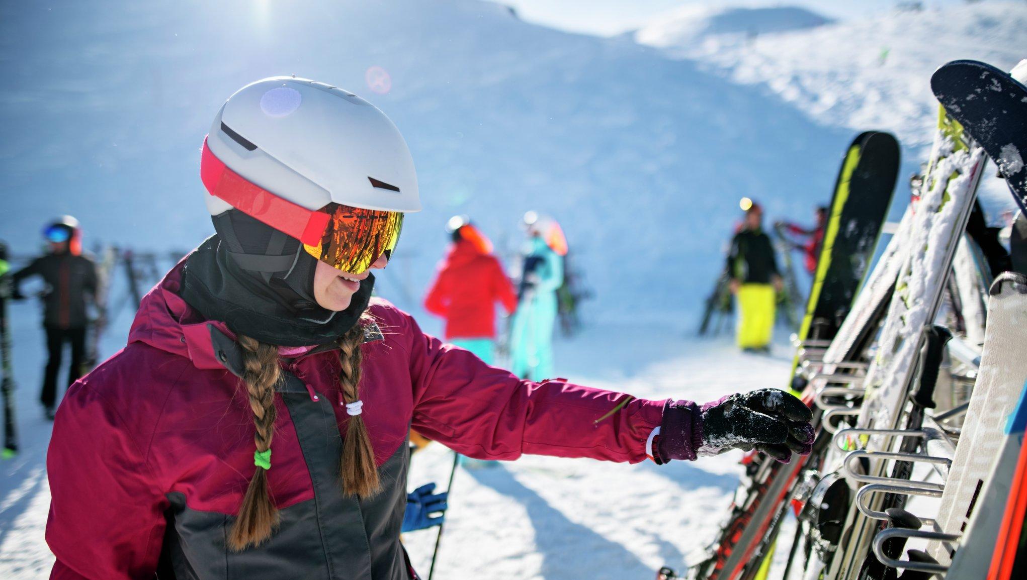 tjej sträcker sig efter skidor