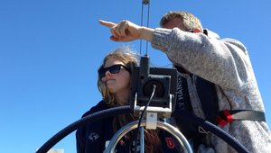 Kaksi henkilöä ohjaa purjevenettä