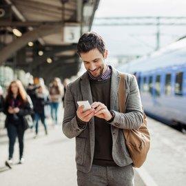 En man med sin mobiltelefon på en tågstation utomlands
