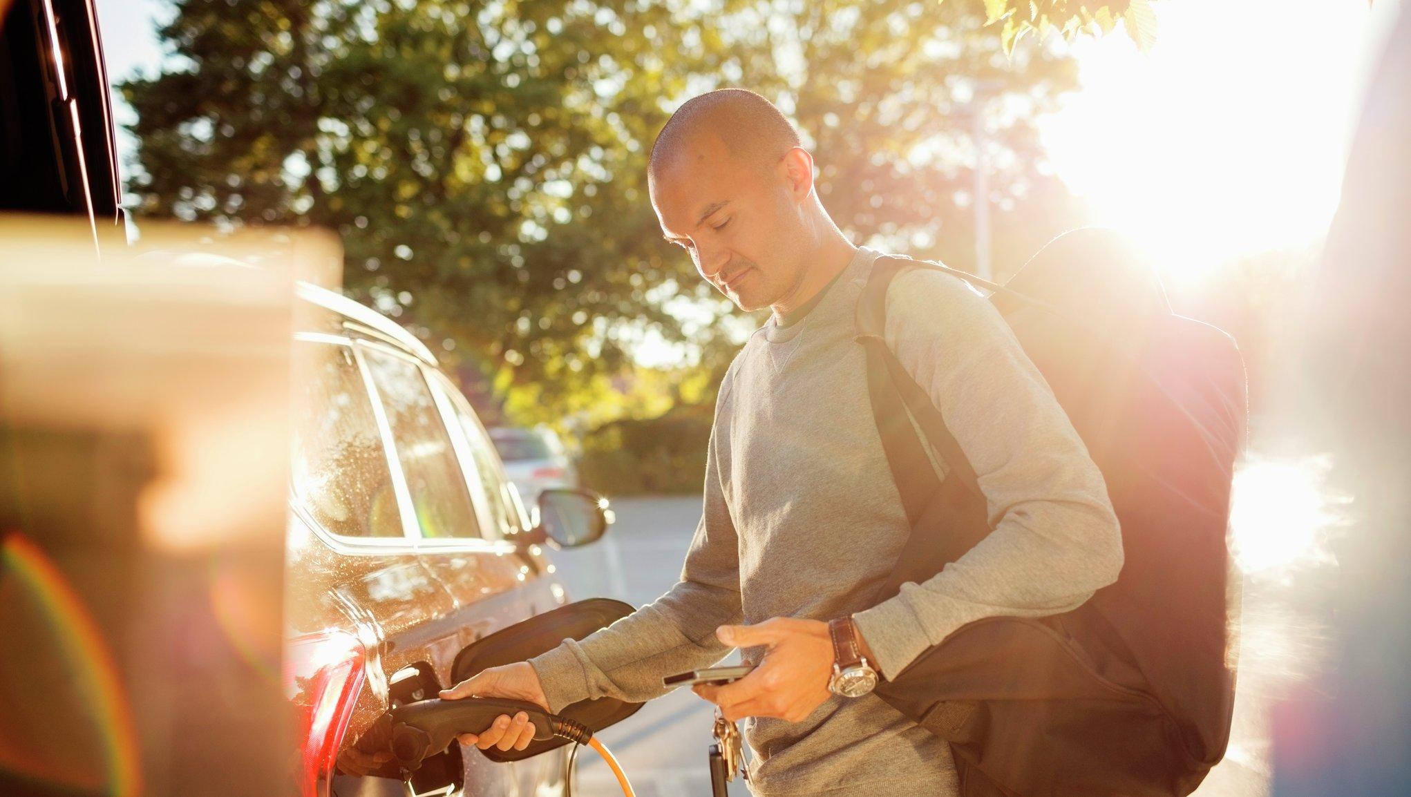 Mann som lader elektrisk bil