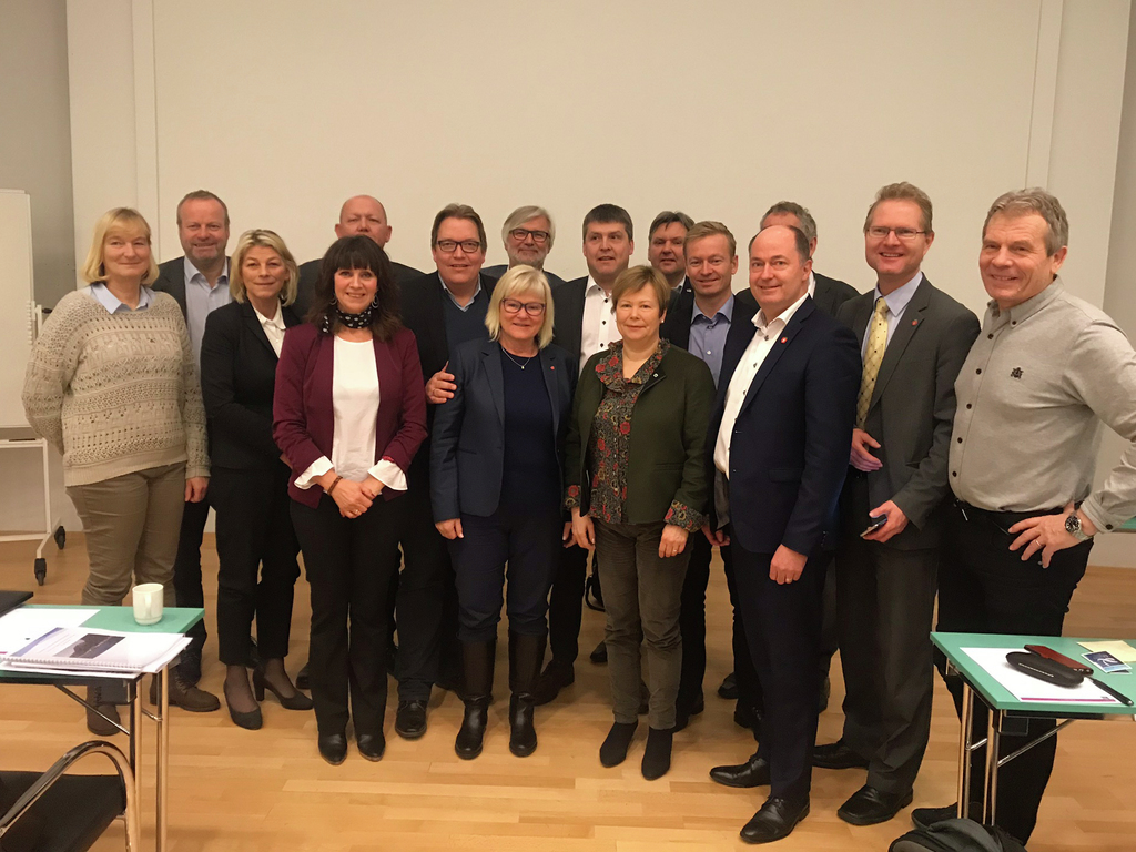 Foto av transport- og kommunikasjonskomiteen i Stortinget på besøk i Sogndal i januar 2018. Her er heile komiteen avbilda saman med fylkesordførar Jenny Følling.