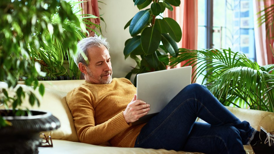 man working with a laptop, sitting on sofa.