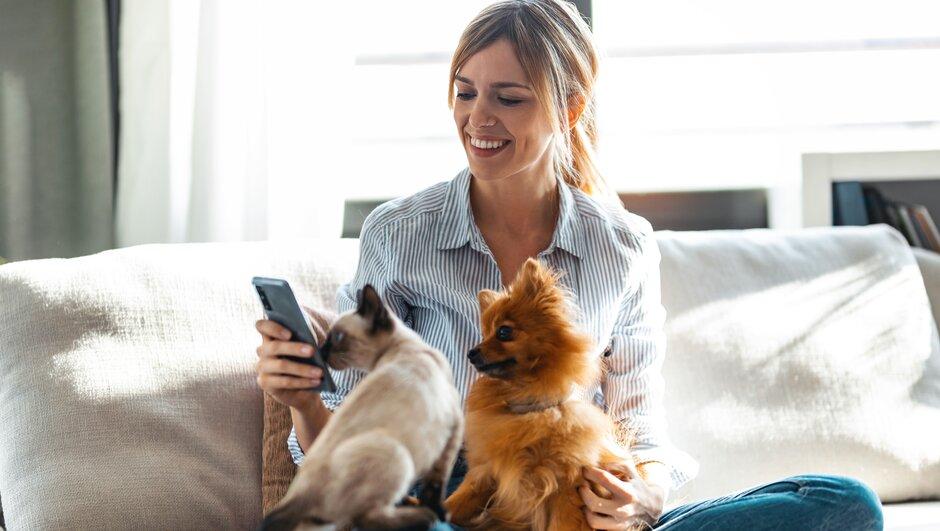 Kvinna med hund och katt ringer Djurens vårdguide