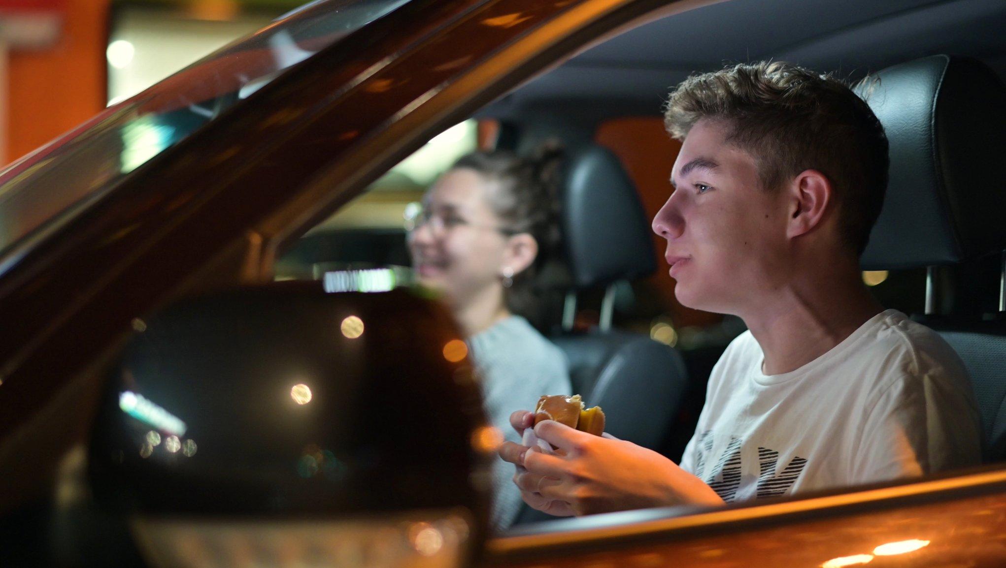 Nainen ja mies autossa, nainen pitelee tablettia