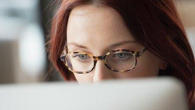Silmälasipäinen nainen katsoo tietokonetta