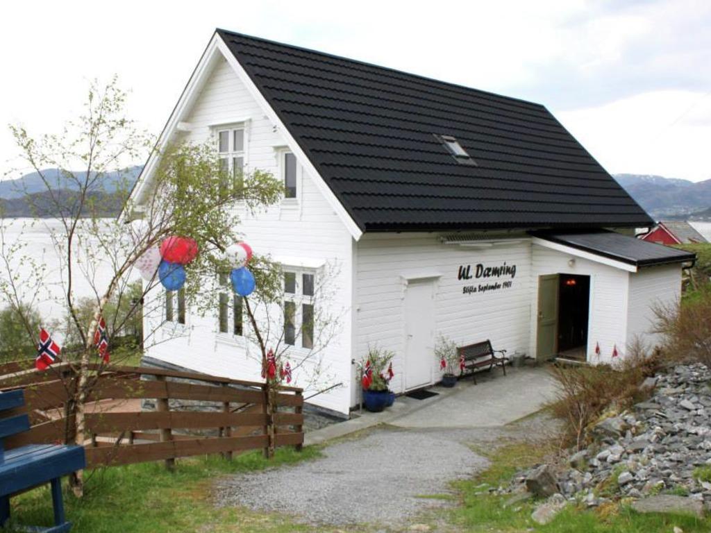 Foto av ungdomshuset Dæmring i Vågsøy. Det er eit kvitt, forholdsvis lite hus, som ser ut til å vere pynta til 17. mai med raude, kvite og blå ballongar, bjørkeris og norske flagg.