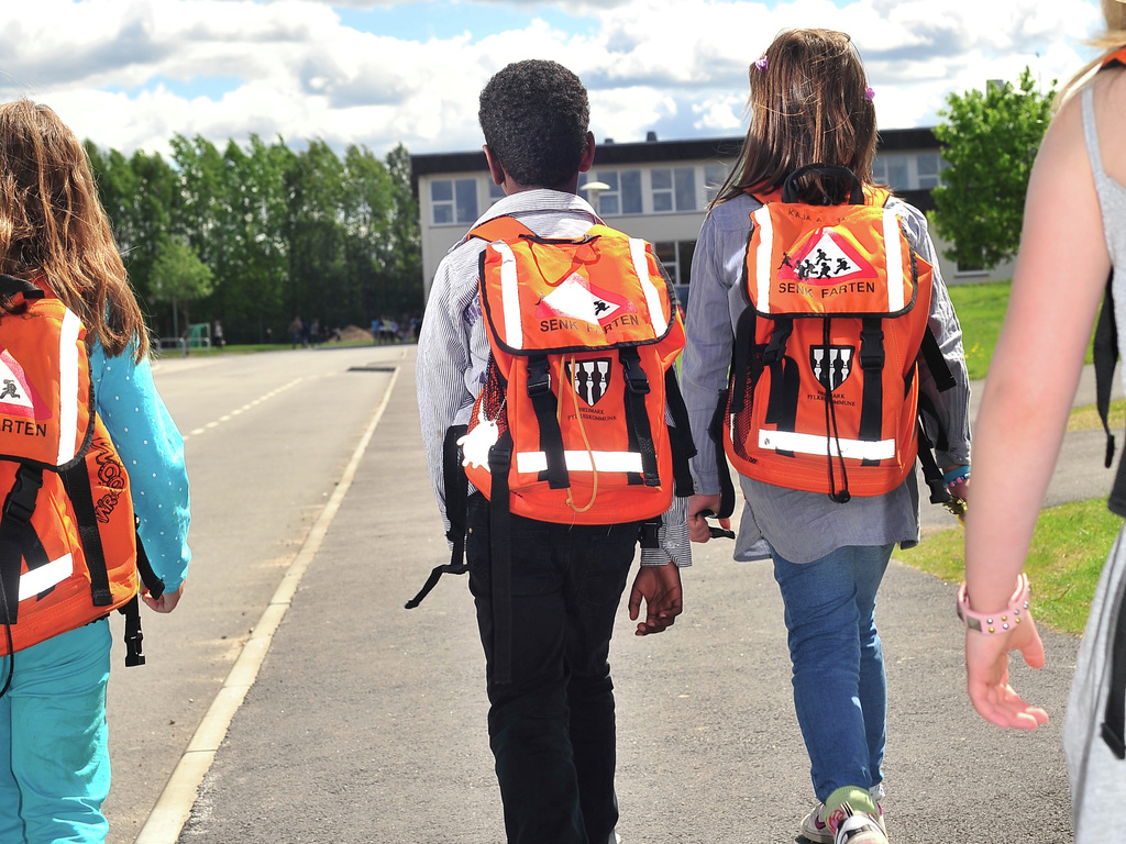 Foto av ungar på skulevegen. Vi ser dei bakfrå, og dei har oransje sekkar med refleks på ryggane sine.