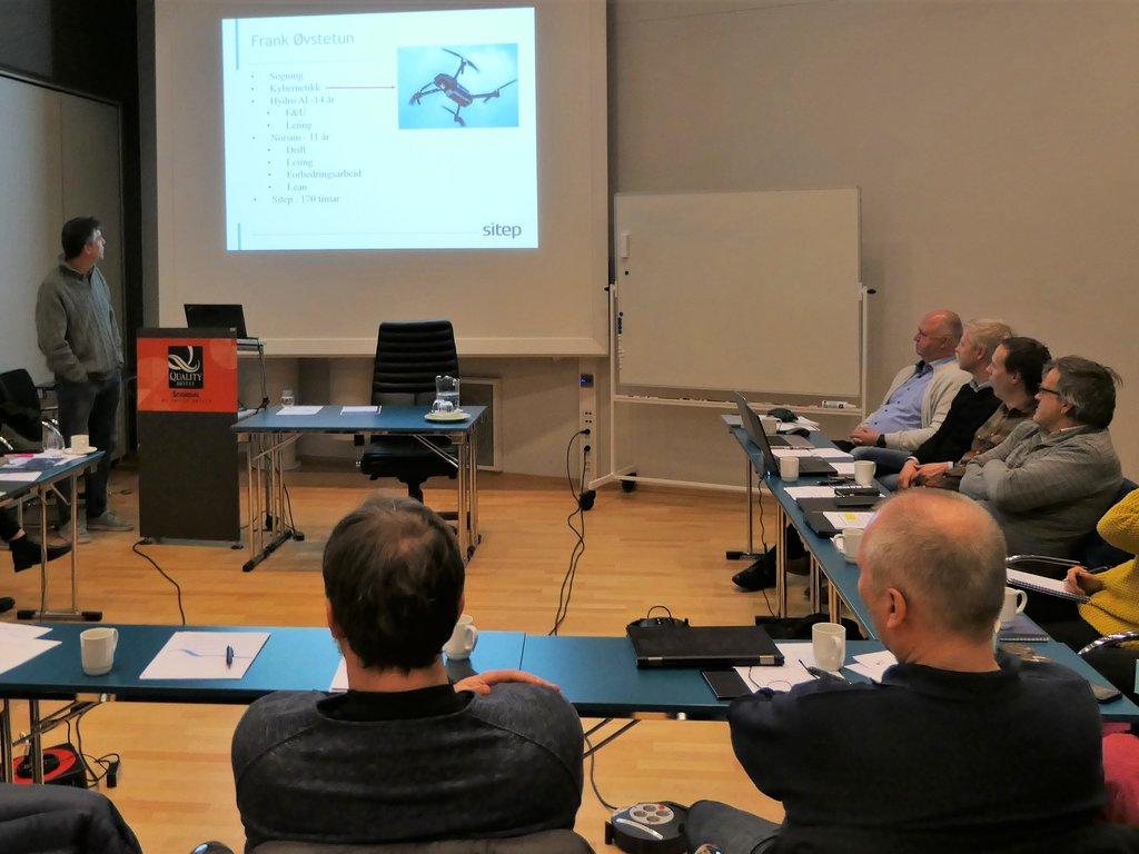 Personar sit rundt eit bord i eit møterom og ser på ein presentasjon.