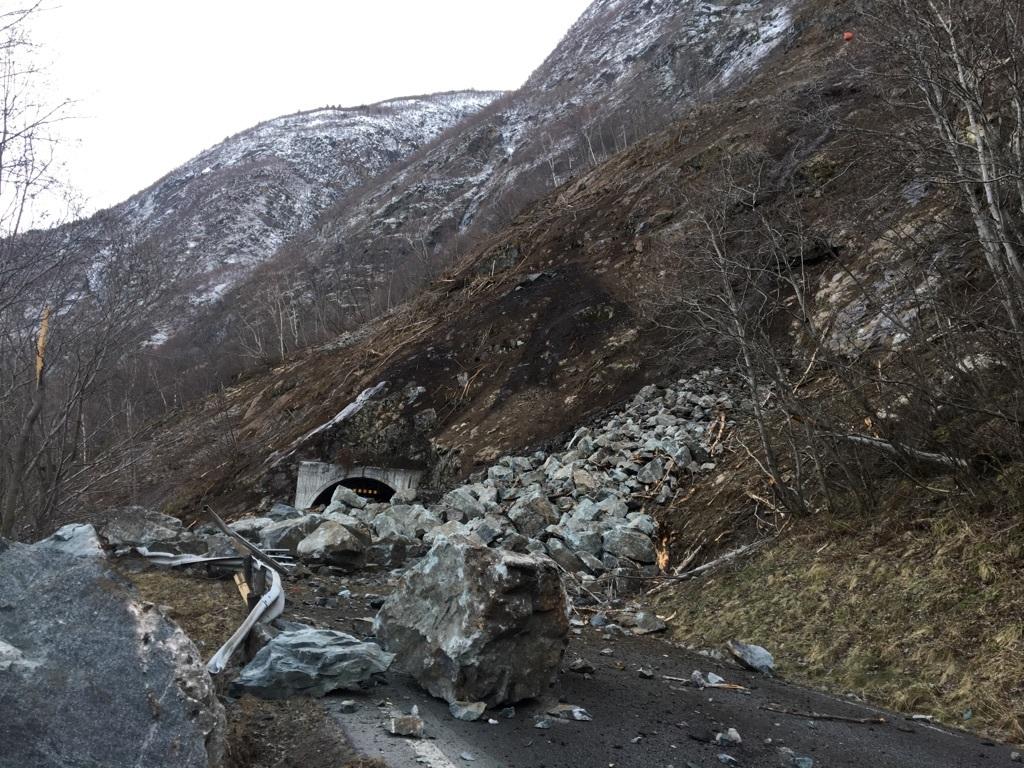 Foto av steinraset som gjekk utanfor Finnsåstunnelen mellom Fodnes og Årdalstangen i januar 2018. Vi ser store stein- og jordmassar og øydelagt autovern i framgrunnen. I bakgrunnen kan vi skimte tunnelopninga.