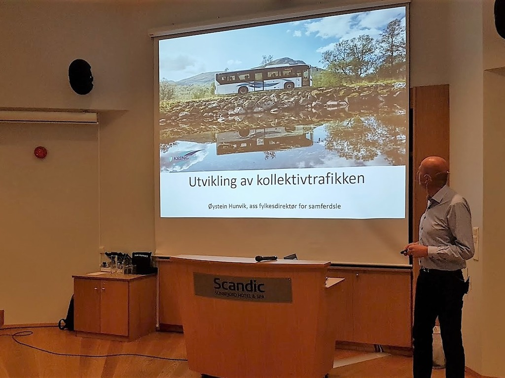 Foto av assisterande fylkesdirektør for samferdsle, Øystein Hunvik, som held ein presentasjon. Vi ser eit lysbilete på veggen, der det er bilete av ein buss, og det står Utvikling av kollektivtrafikken.