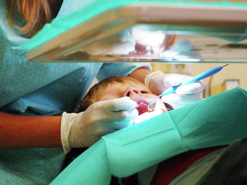 Foto av ein gut i tannlegestolen med ein tannlege som undersøker tennene hans.