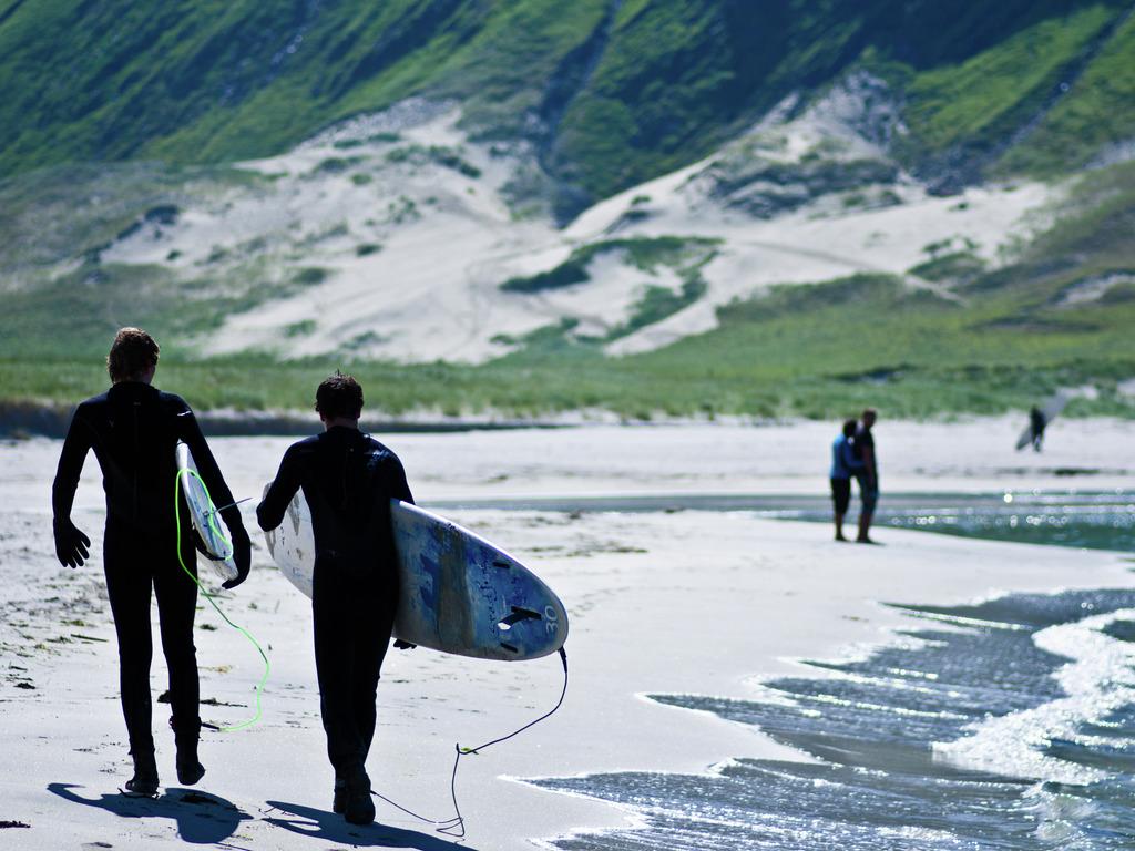 Foto av surfarar i Hoddevika på Stadlandet. Vi ser to surfarar bakfrå, som går i strandkanten med kvart sitt surfebrett. Det er sommar og fint vêr.