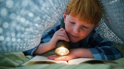 poika lukee taskulampun valossa
