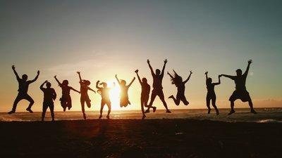 Hyppivien ihmisten siluetteja rannalla