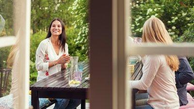 kvinnor sitter ned vid matbord på uteplats