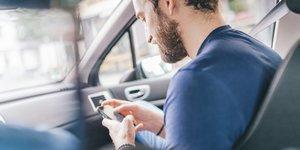 Mies autossa katsomassa kännykkää