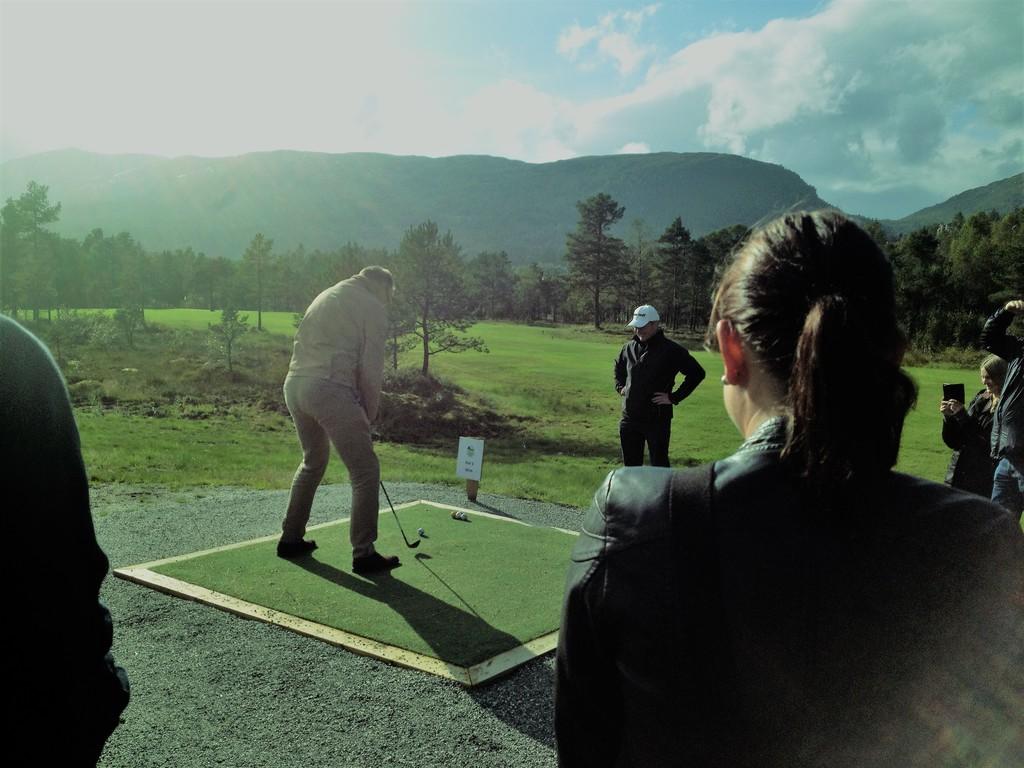 Foto som syner ein golfspelar som står krøka med kølla klar til eit lite slag. Det står andre menneske rundt, det er grønt gras og sol.