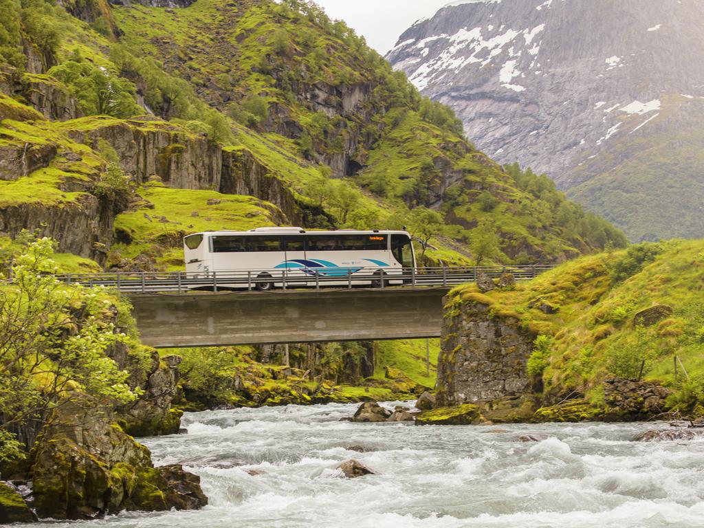 Foto av ein buss merka med Kringom, som køyrer i knallgrøn natur ein sommardag. Det er ei elv som renn mot går under brua der bussen køyrer.