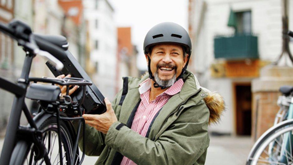 äldre man tar bort batteri på elcykel