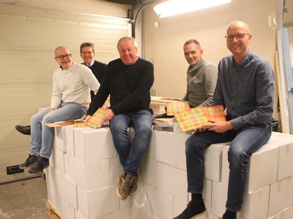 Foto av fem menn som sit oppå kassar med dagsturhyttebrosjyrer. Dei held også brosjyrer i hendene.