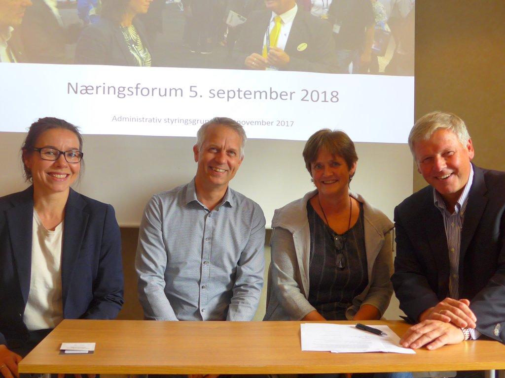 Fire personar sit og smiler ved eit bord. Det er Kristine Kopperud Timberlid, Philip Lorentzen, Mette Rønning og Jan Heggheim. Dei har underteikna ein samarbeidsavtale som ligg på bordet.