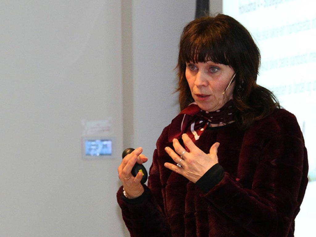 Foto av fylkesordførar Jenny Følling, som snakkar i ein mikrofon. Ho er kledd i mørke kle og har eit tørkle rundt halsen.
