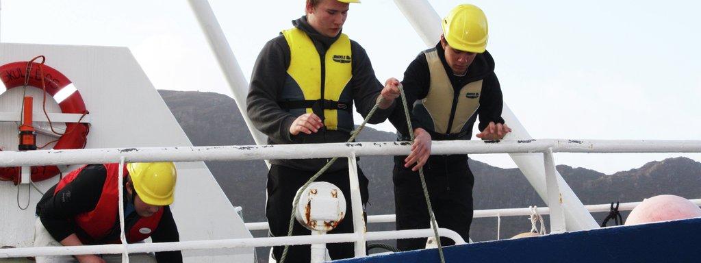 Foto av tre elevar som har undervisning på opplæringsfartøyet Skulebas. Dei har redningsvest og gule hjelmar på.