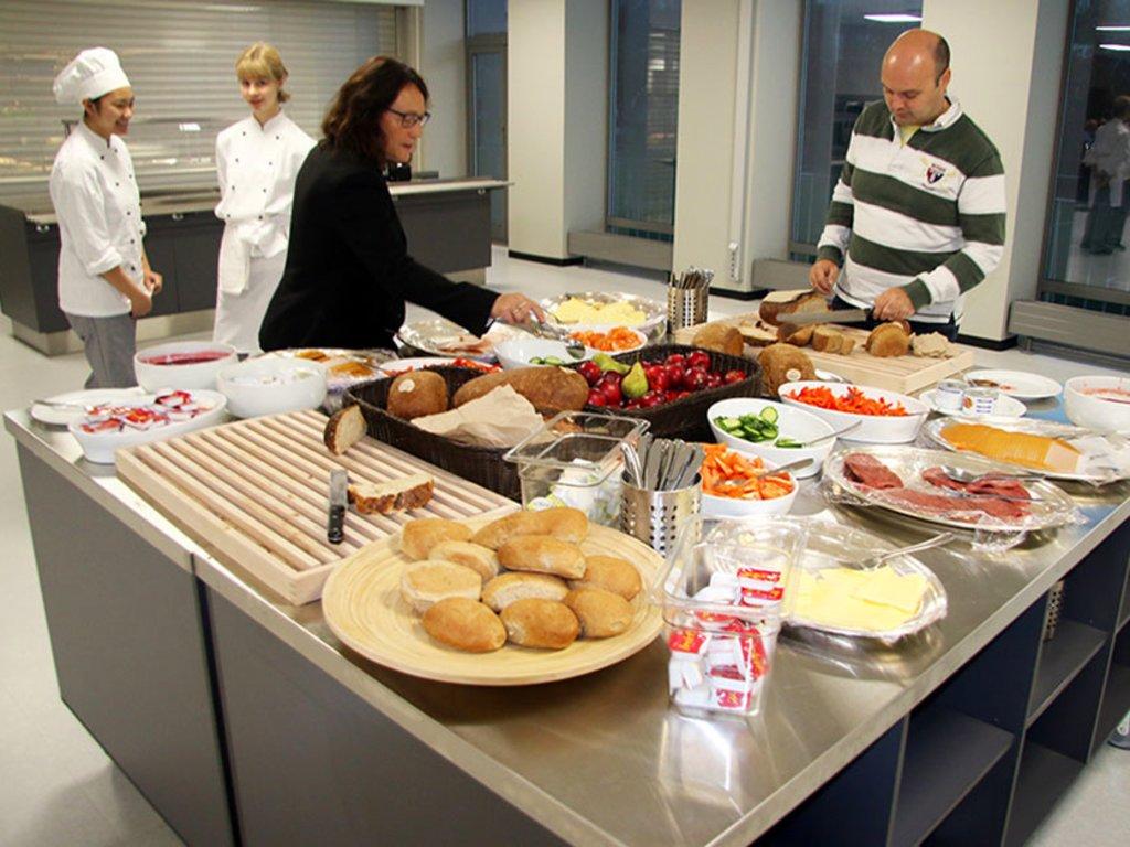 Foto av to personar som forsyner seg av frukostbord på ein vidaregåande skule.